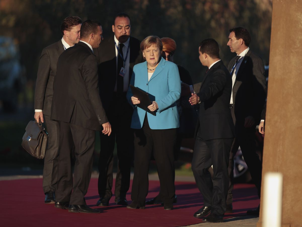 The Latest: German court rejects case against migration pact