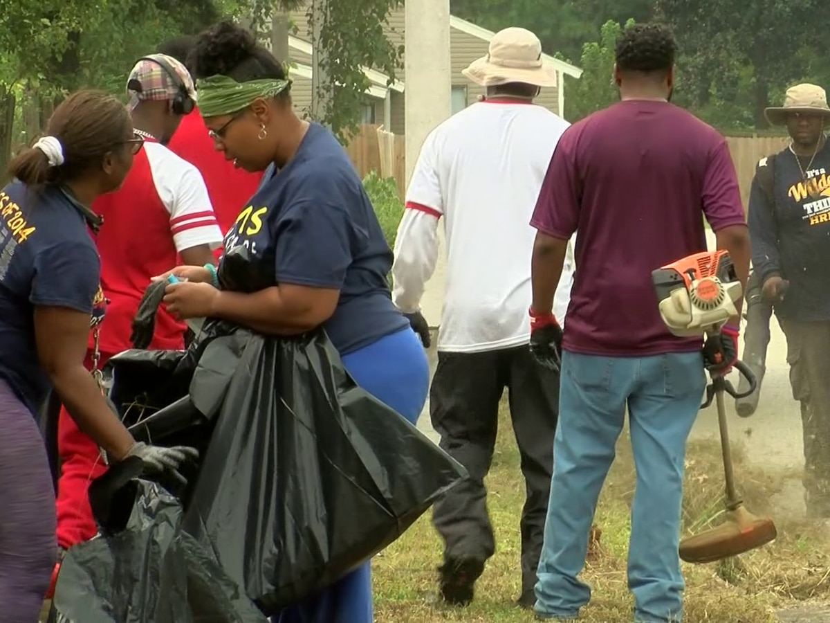 Volunteers help mow grass around Hickory Ridge Middle School