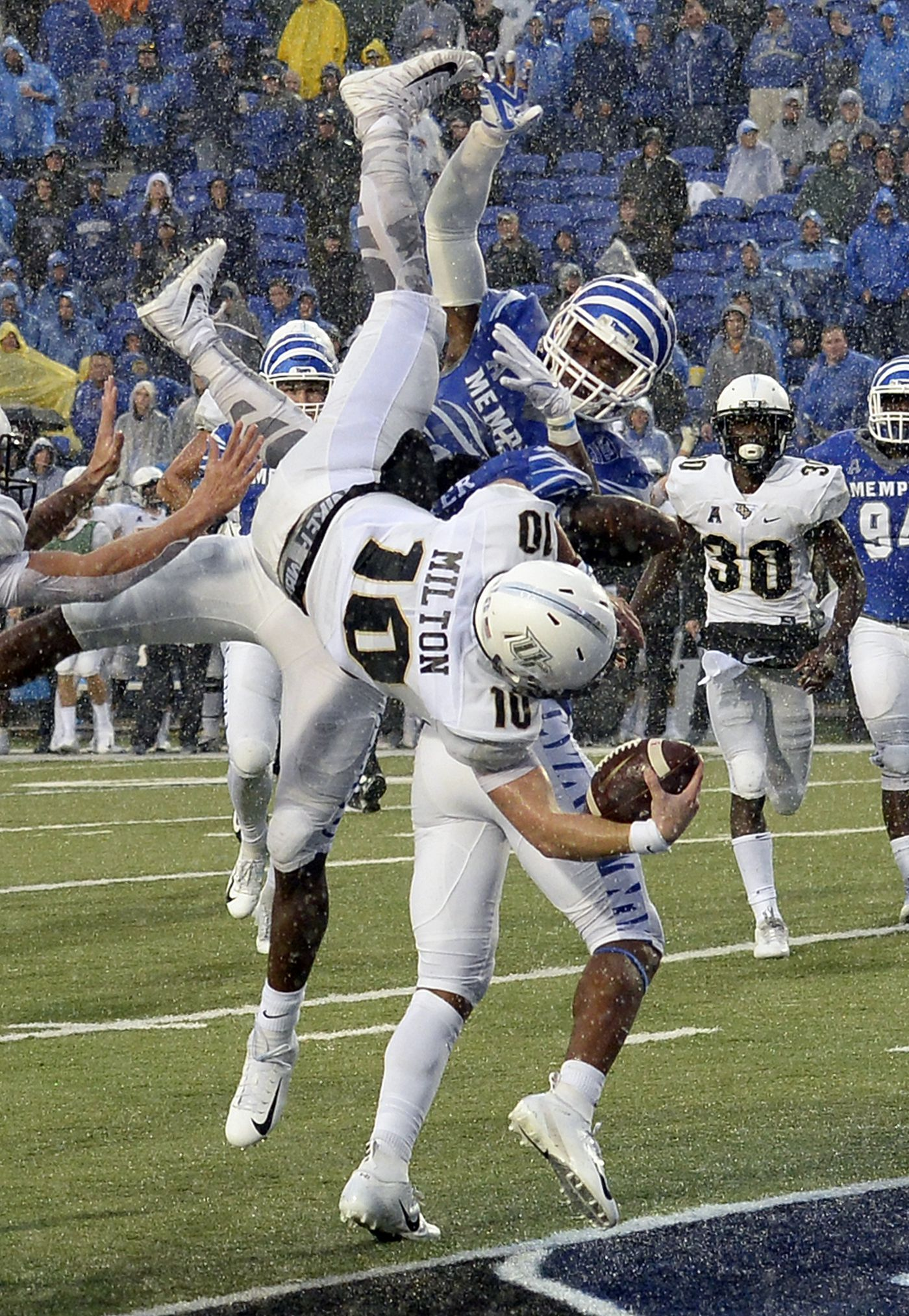 Central Florida quarterback McKenzie Milton (10) dives over Memphis  defensive back Josh Perry ( 6d2616cbc